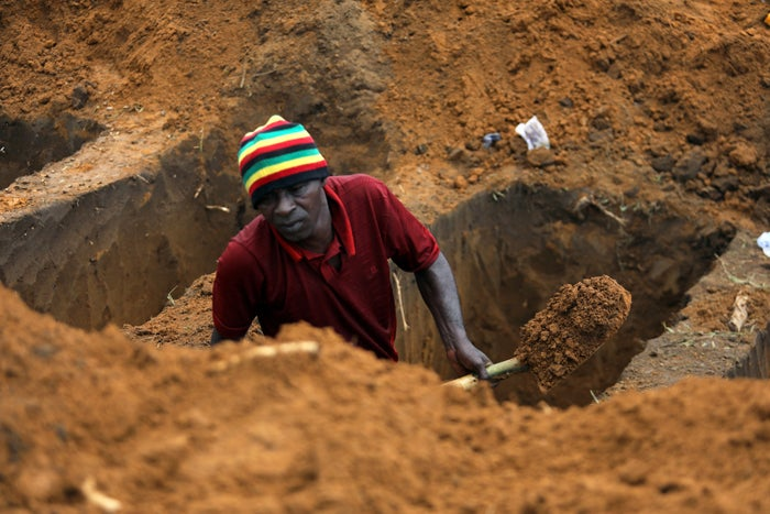 A worker digs graves at a cemetery.