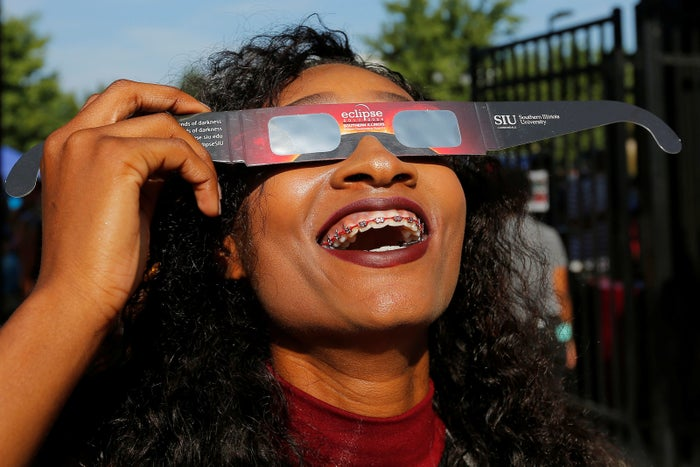 A cheerleader uses solar viewing glasses before welcoming guests to watch the total eclipse at Southern Illinois University's football stadium in Carbondale, Illinois.