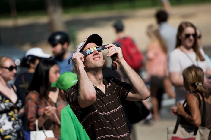 A man tests special solar glasses outside the Smithsonian's Air and Space Museum on the National Mall before the eclipse on Aug. 21 in Washington, DC.