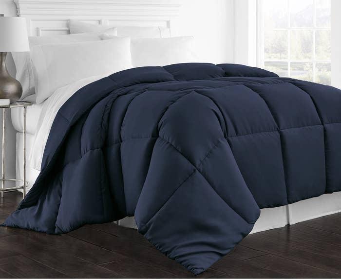 Navy blue comforter on mattress in bedroom