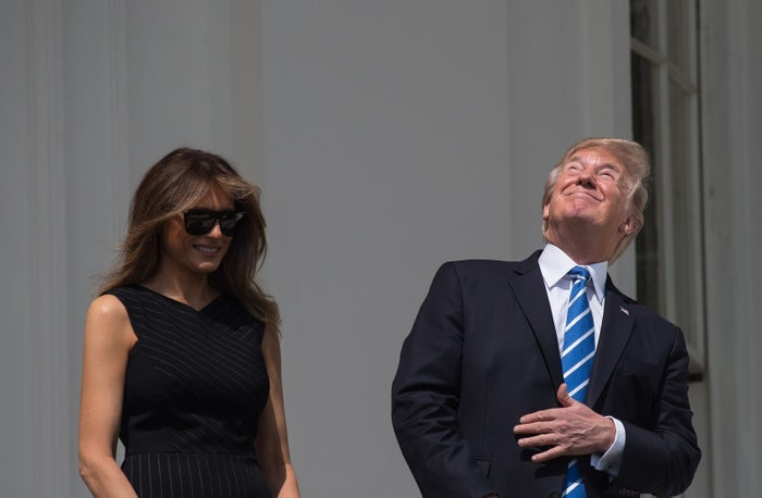 President Donald Trump and first lady Melania Trump look up at the partial solar eclipse from the balcony of the White House on Aug. 21.