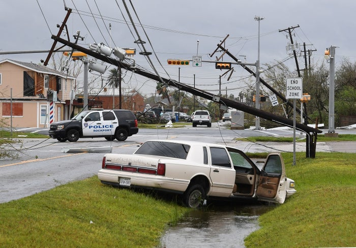 A car lies abandoned near downed telephone polls in Rockport, Texas, on Saturday.