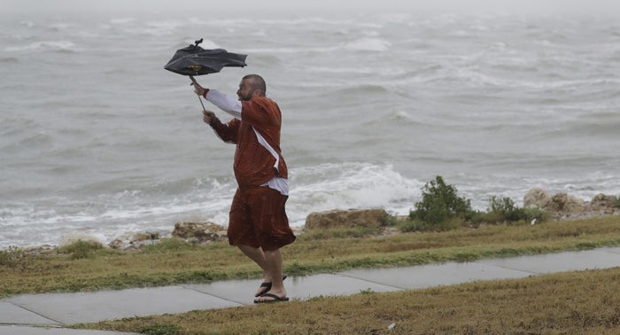 A man braves the wind and rain in Corpus Christi, Texas, on Friday.