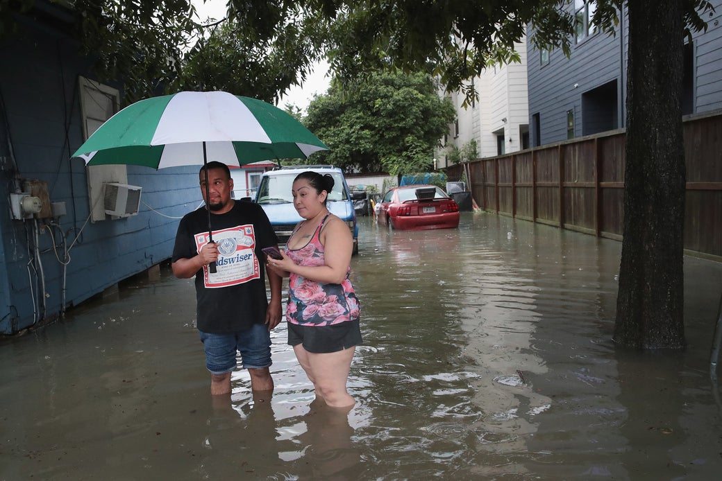 Vincente Navas (left) and Alma Barrientos stand outside their home in the Cottage Grove neighborhood which has been inundated with flooding from Hurricane Harvey on Aug. 27, 2017 in Houston.