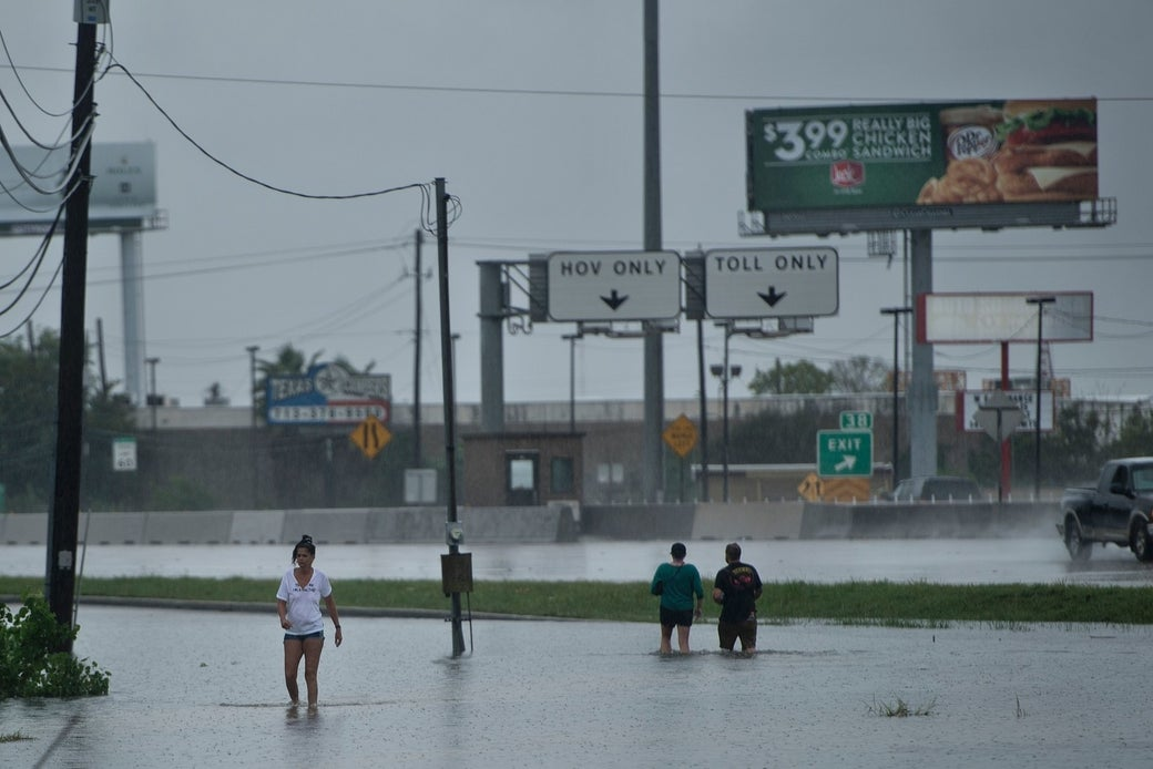 People walk through flooded streets during the aftermath of Hurricane Harvey Aug. 27, 2017 in Houston.