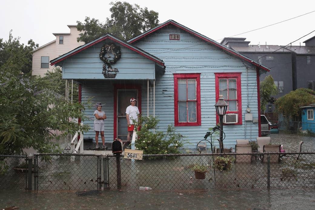 Las personas en el porche observan mientras las lluvias del huracán Harvey inundan el vecindario de Cottage Grove, el 27 de agosto de 2017, en Houston.