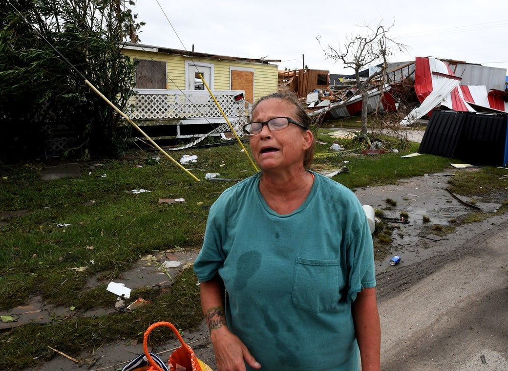 Local resident Kathy Neihaet walks through her damaged neighborhood after Hurricane Harvey hit Port Aransas, Texas, on Aug. 27, 2017.