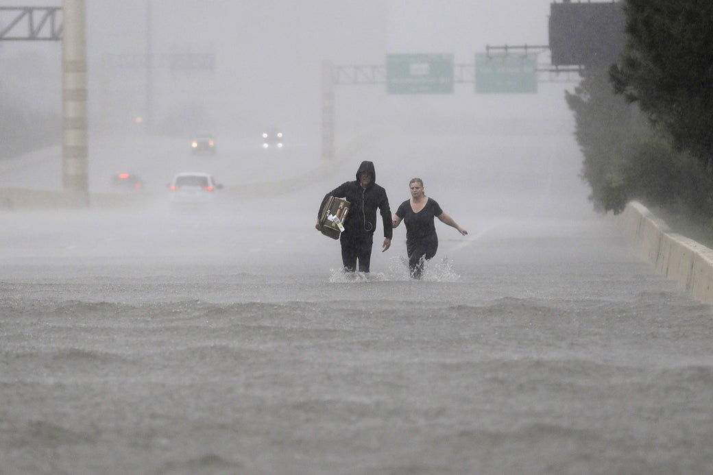 Two people walk down a flooded section of Interstate 610 in floodwaters from Tropical Storm Harvey, Aug. 27, 2017, in Houston.