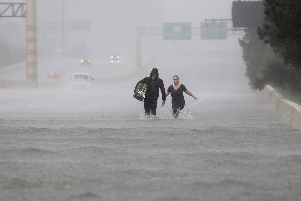 Dos personas caminan por una sección de la Interestatal 610 inundada a causa de la tormenta tropical Harvey, 27 de agosto de 2017, en Houston.
