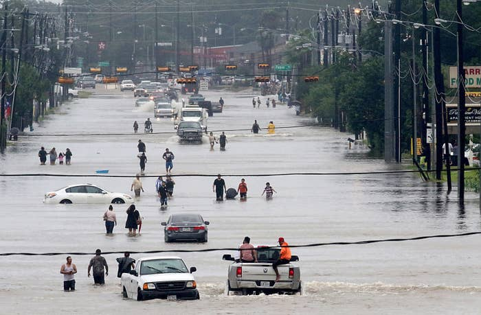 People walk through the flooded waters of Telephone Road in Houston on Aug. 27, 2017.