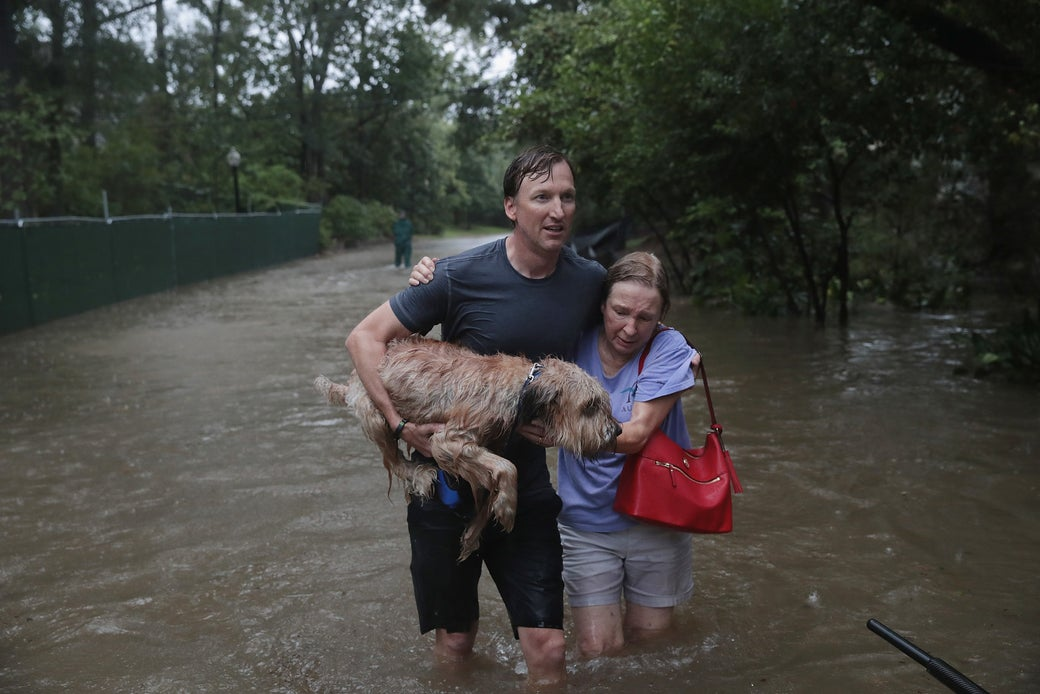 Andrew White (left) helps a neighbor down a street after rescuing her from her home in his boat in the upscale River Oaks neighborhood after it was inundated with flooding from Hurricane Harvey on Aug. 27, 2017 in Houston.