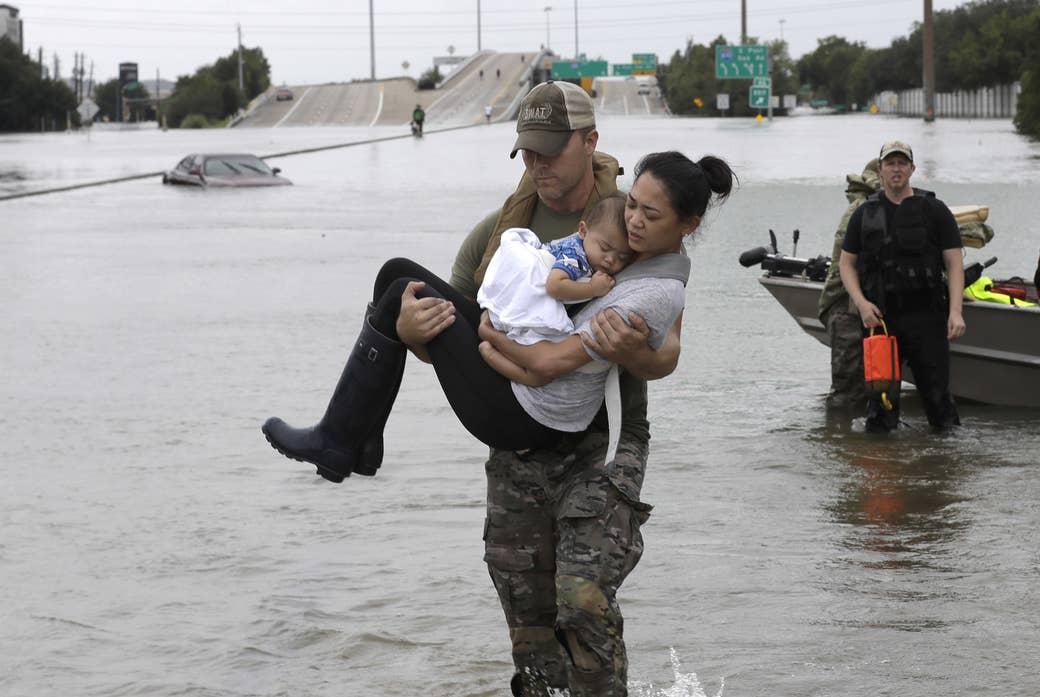 Daryl Hudeck, oficial de la unidad SWAT de la policía de Houston, lleva a Catherine Pam y a Aiden, su hijo de 13 meses, luego de rescatarlos de su hogar rodeado por las aguas de la tormenta tropical Harvey, el domingo 27 de agosto de 2017, en Houston.