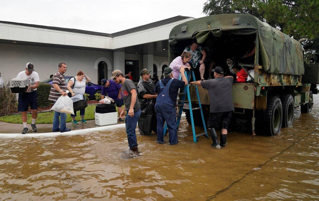 Voluntarios suben a personas a un camión militar antiguo de colección para evacuarlas de la inundación causada por el huracán Harvey en Dickinson, Texas, el 27 de agosto de 2017. REUTERS/Rick Wilking