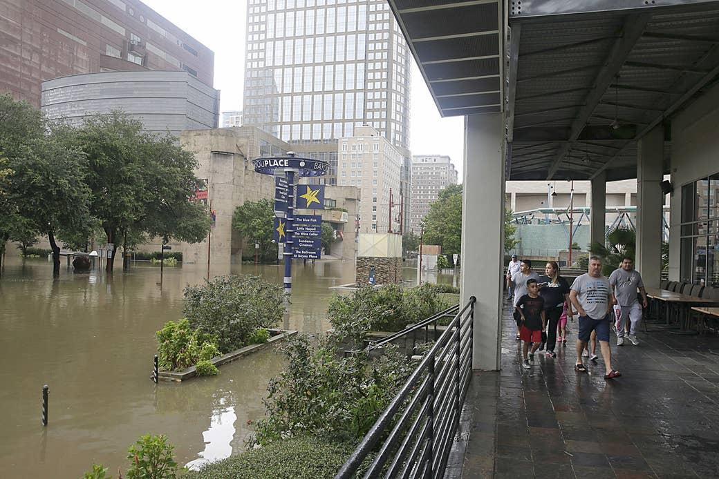 Personas caminando por Bayou Place mientras observan el inundado distrito teatral de Houston, el 27 de agosto de 2017 mientras la ciudad lucha con la tormenta tropical Harvey y las inundaciones resultantes.