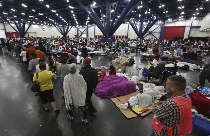 People line up for food and others rest at the George R. Brown Convention Center in Houston on Aug. 29.