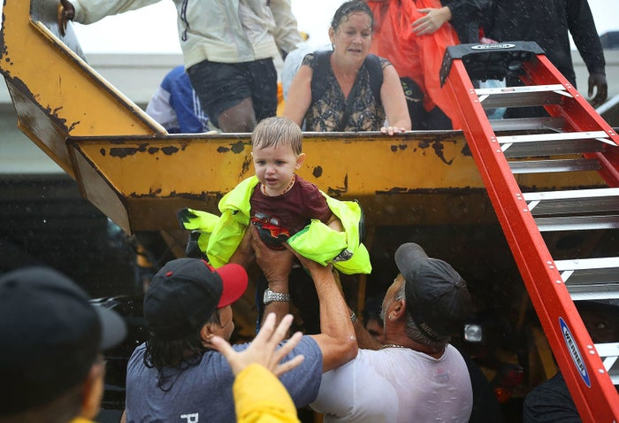 A child is helped off the back of a rescue truck after his family was evacuated in Houston on Aug. 28.