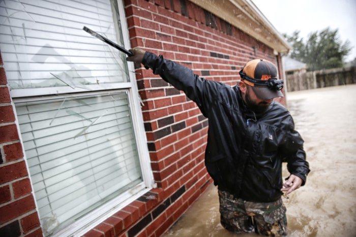 Jan Tullos, 32, from College Station, Texas, smashes the window on a flooded home in an attempt to rescue a woman reportedly stuck inside with a broken leg, in Clodine, Texas, on Aug. 28.