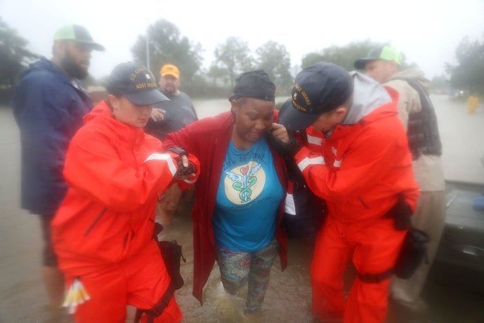 Coast Guard officials help a woman who was rescued from her flooded home in Houston on Aug. 28.