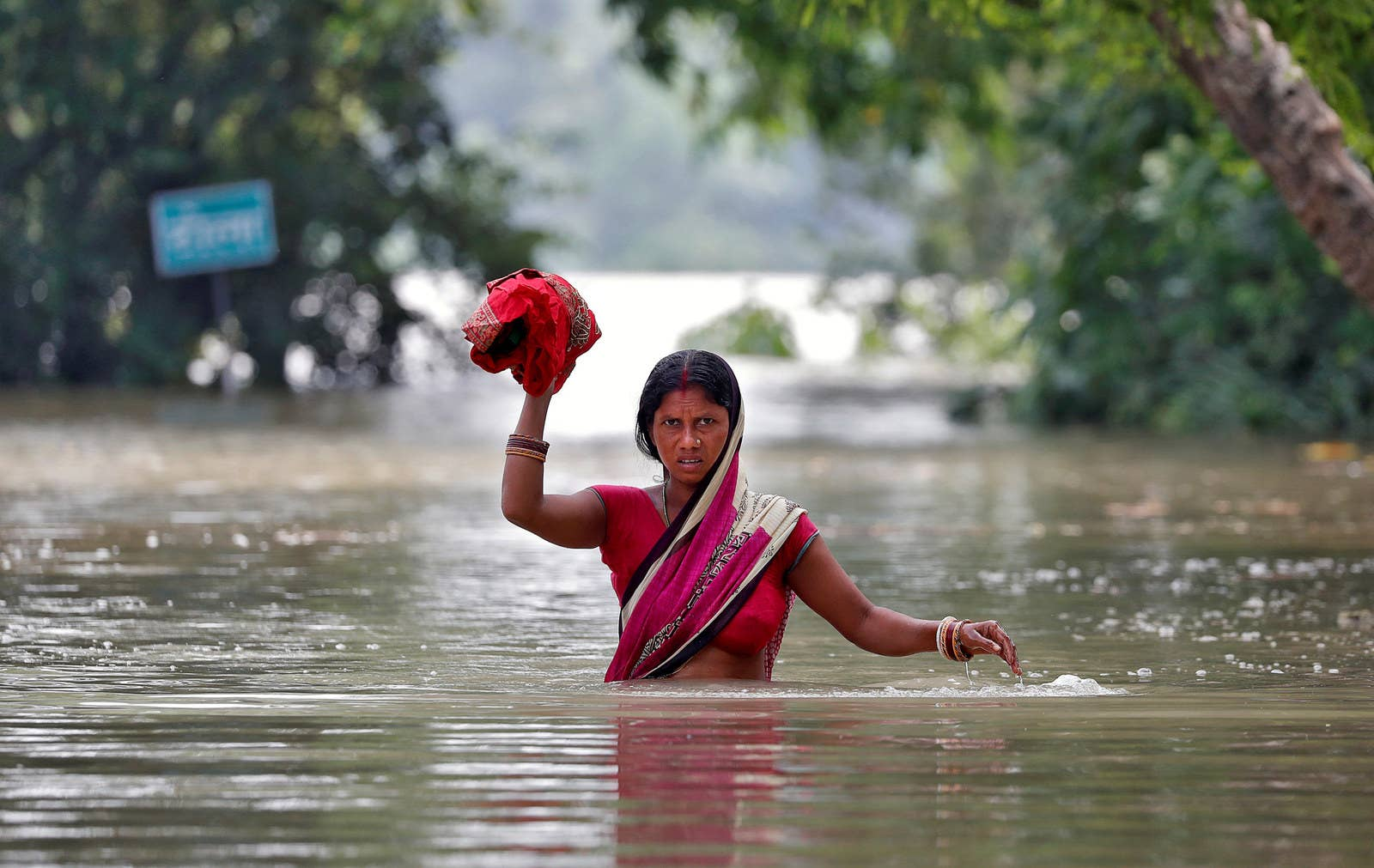 A woman wades through a flooded village in Bihar, India.