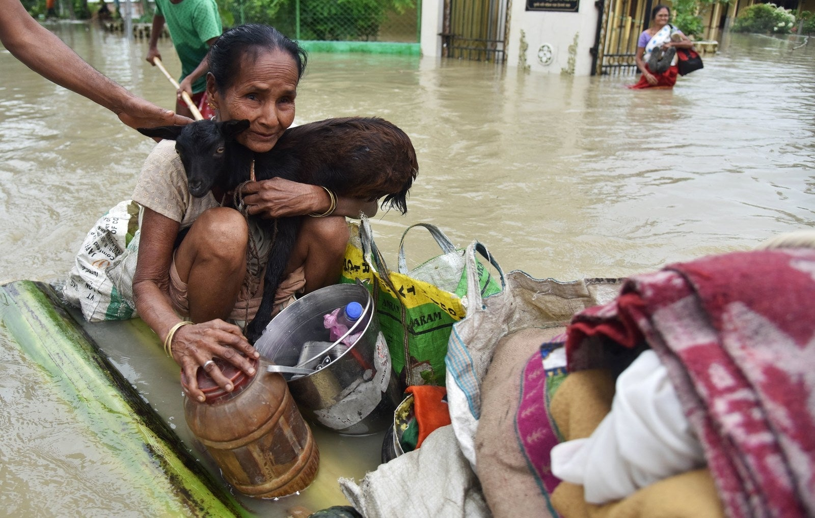 An Indian woman holds a goat while sitting on a makeshift raft in Koliabor village in Assam.
