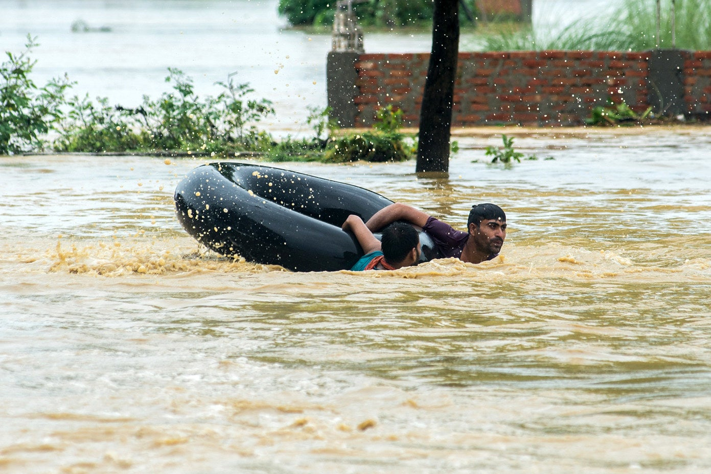Nepalis swim with a rubber ring in a flooded area in Parsa district.