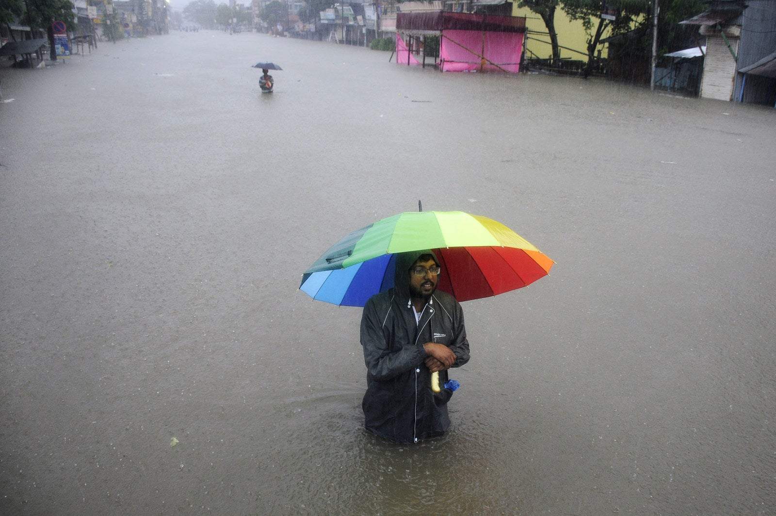 A man walks through a flooded street during a heavy downpour in the northeastern Indian state of Tripura.