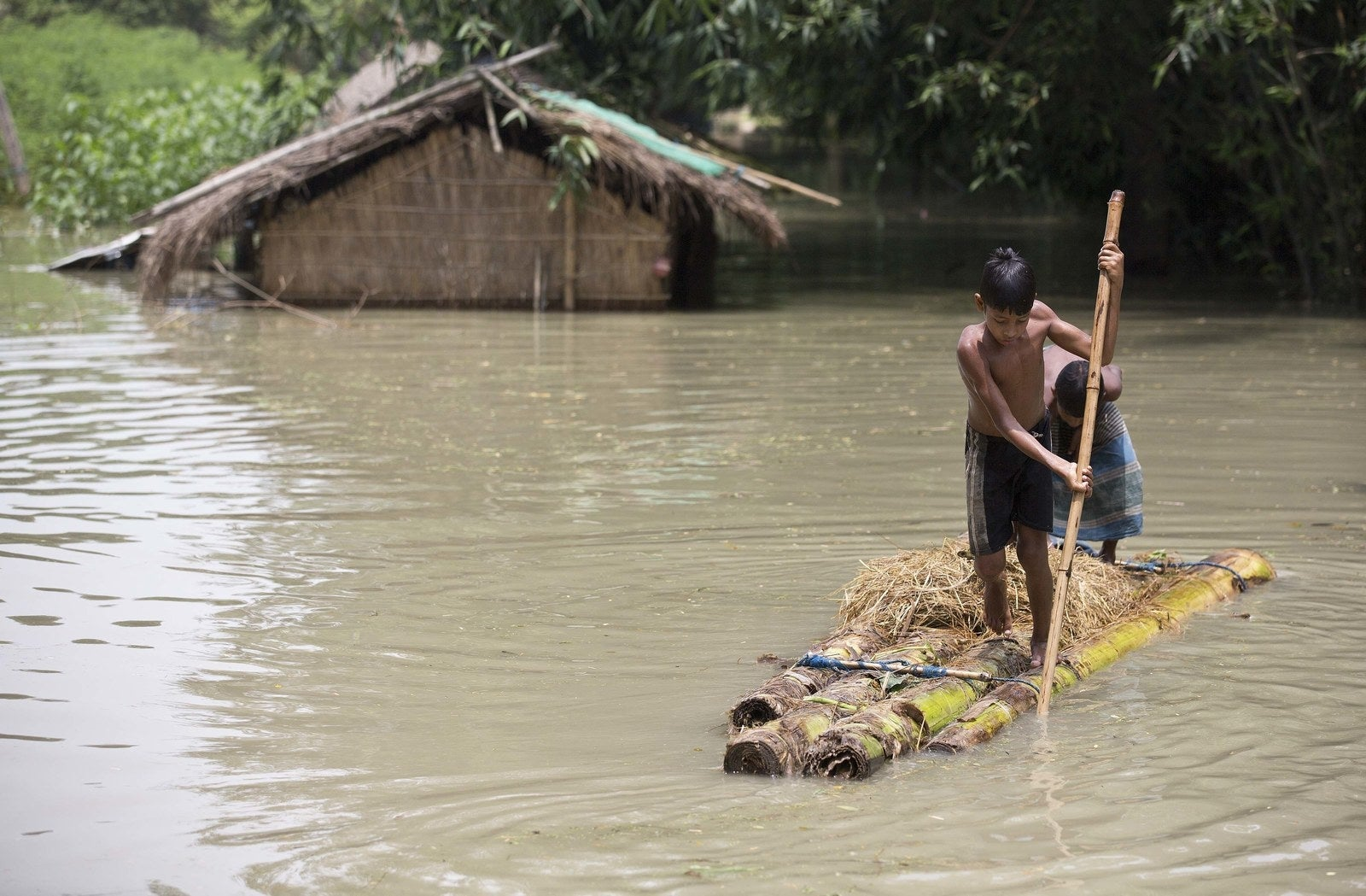 Two boys stand on a banana raft in Assam, India. At least 850 people have been killed in the flood-affected states across the country.