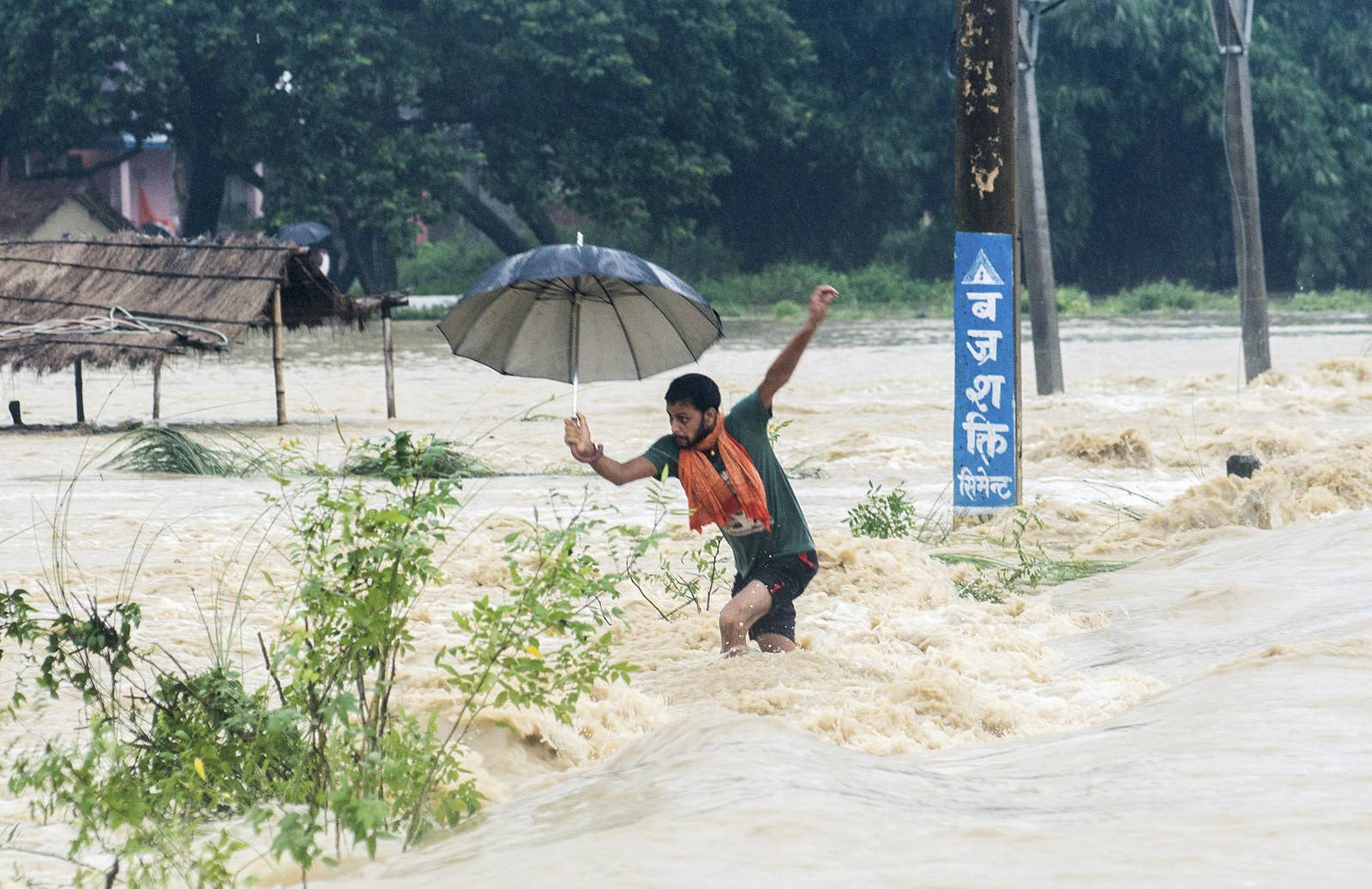 A man tries to cross a flooded street in Birgunj, Nepal. Heavy rains have hit more than a dozen districts in the country's far eastern region as well as some areas in the west.