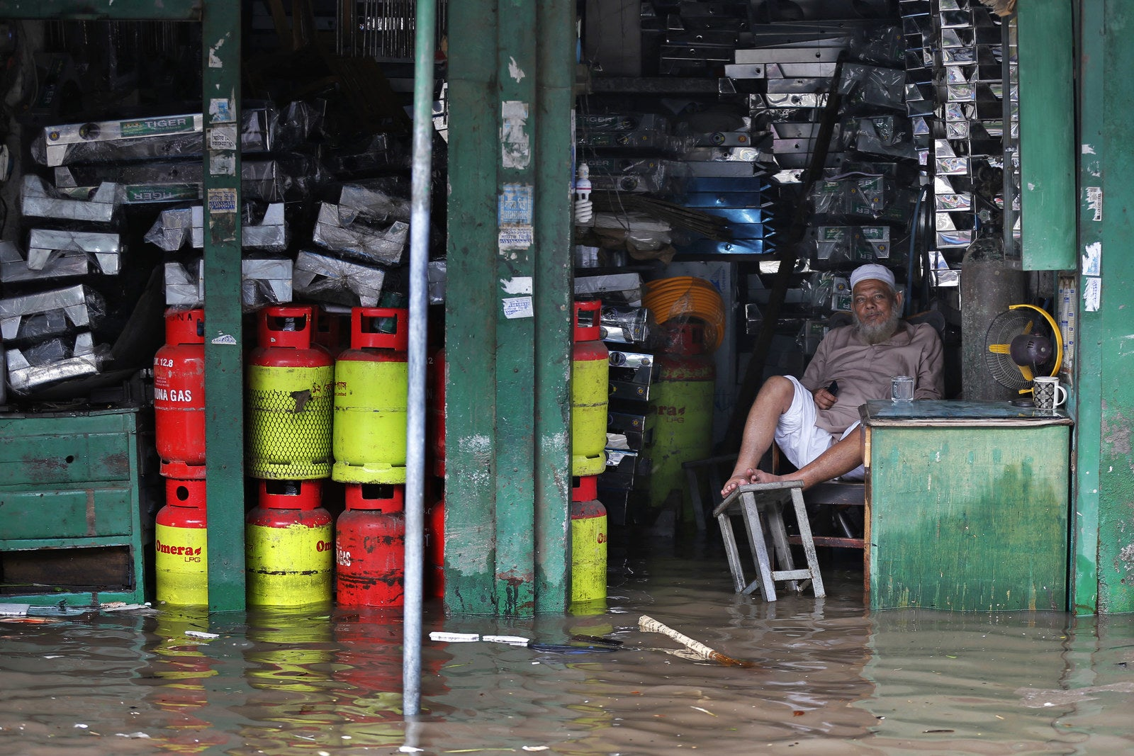 A Bangladeshi man sits in his flooded shop after heavy rain in Dhaka.