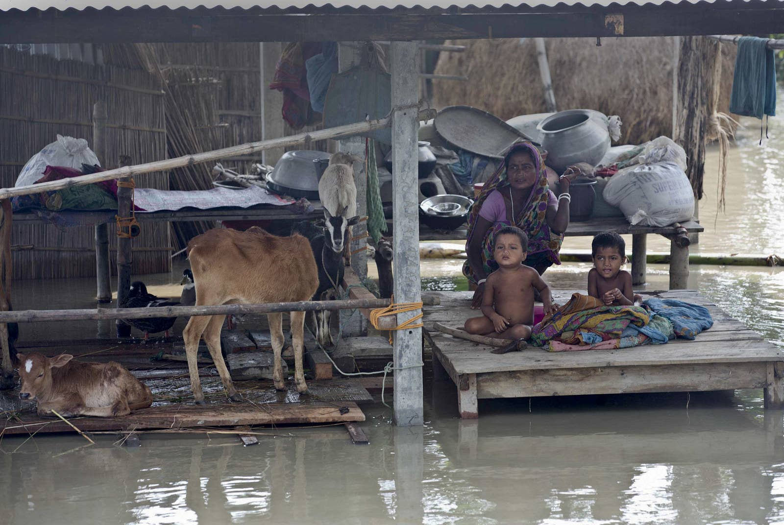 Flood victims wait for relief supplies in a village east of Gauhati in the northeastern Indian state of Assam.
