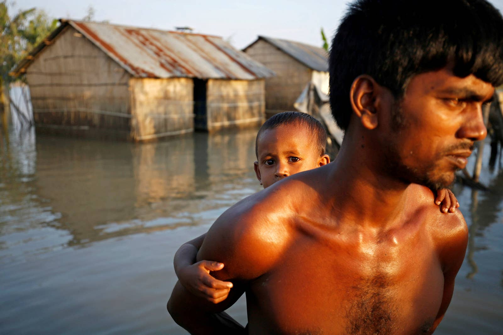 A child and his father walk through a flooded area in Bogra, Bangladesh.