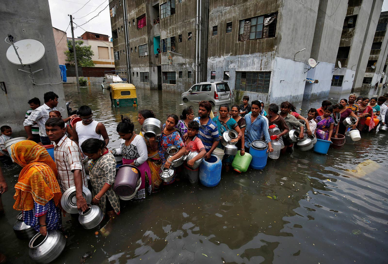 People wait in a line to collect drinking water from a municipal tanker at a flooded residential colony in Ahmedabad, India.