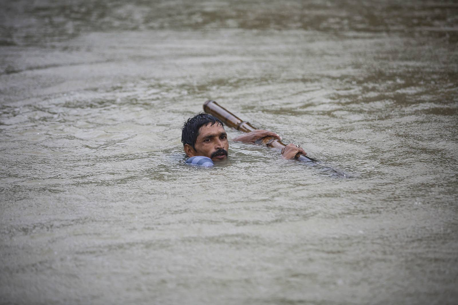 A Nepali man tries to cross flood water at Topa village in Saptari district.