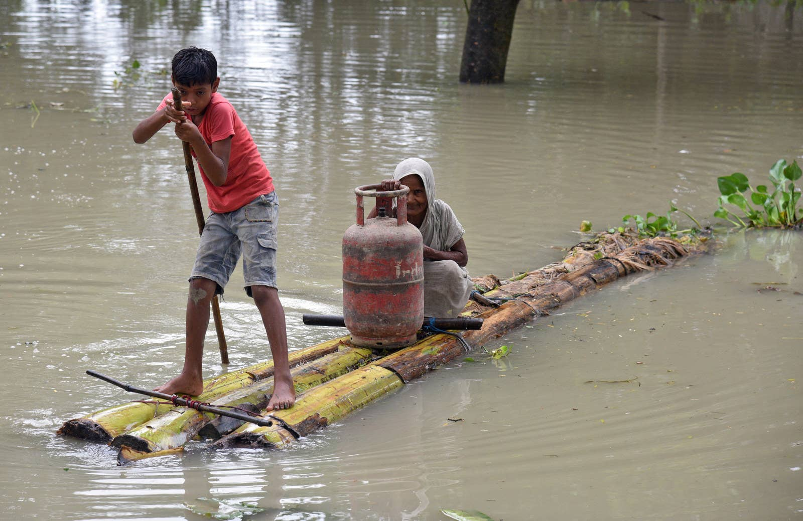 A boy rows a makeshift raft as he transports a woman and a cooking gas cylinder through the flood waters in Assam, India.