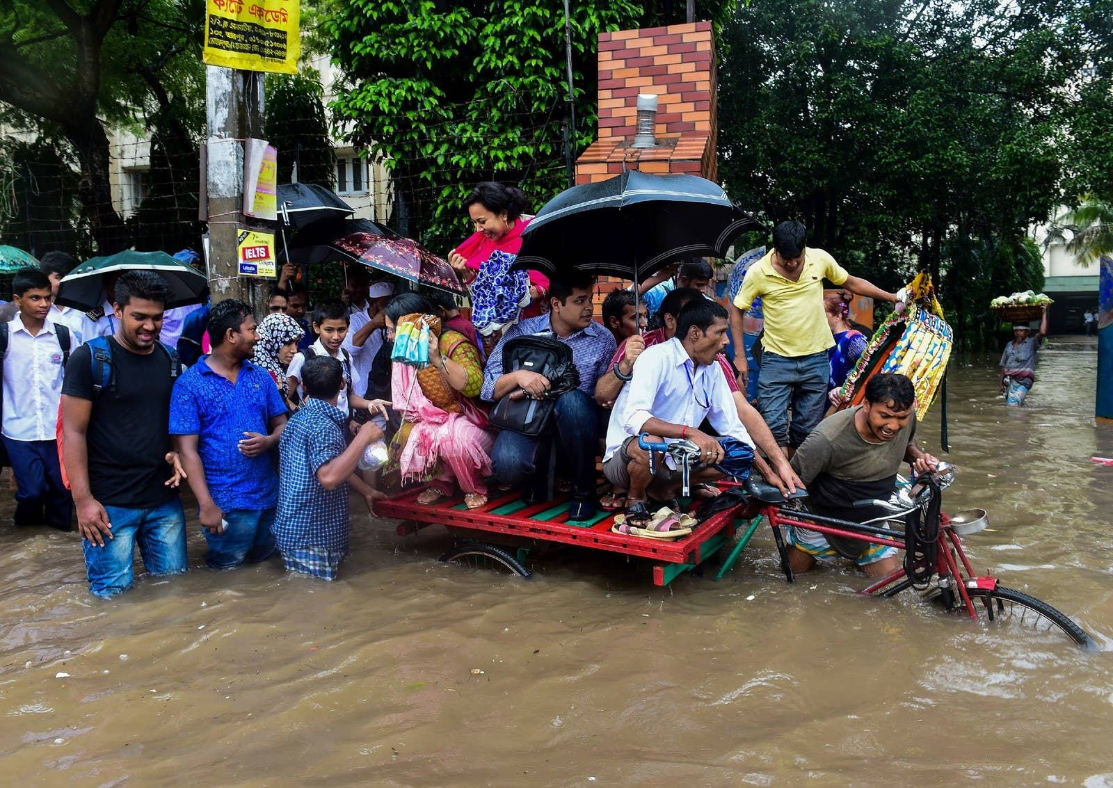 Bangladeshi commuters use a rickshaw to cross a flooded street in Dhaka.