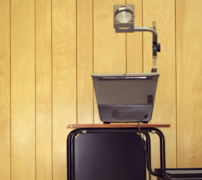 A projector on a desk in front of a wood paneled wall