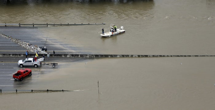 A boat travels along Interstate 10 as floodwaters from Tropical Storm Harvey cover a portion of the highway in Houston.