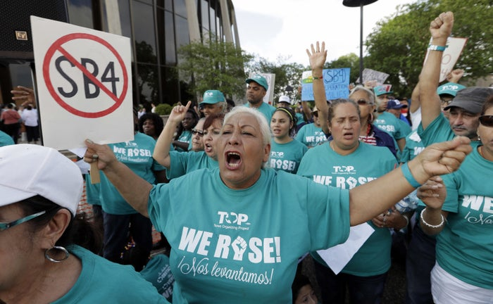 """Merced Leyua, center, joins other protesters outside the Federal Courthouse to protest Texas' """"sanctuary cities"""" bill SB 4."""