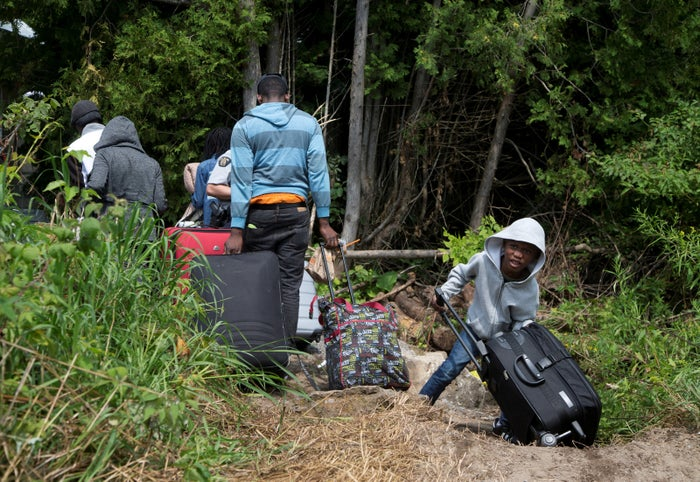 A family claiming to be from Haiti drags their luggage over the US-Canada border on Aug. 3, 2017.