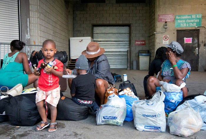 A group of Haitian asylum seekers sit with shopping bags outside the Olympic Stadium in Montreal.