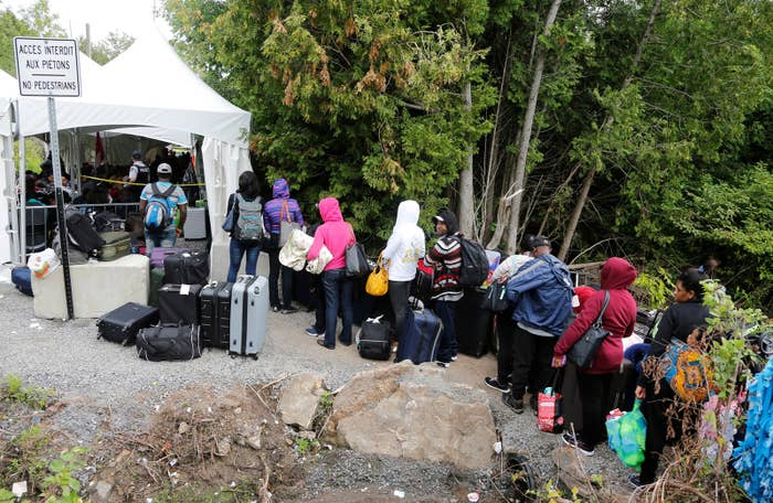 A line of asylum-seekers who identified themselves as from Haiti wait to enter into Canada from Roxham Road in Champlain, New York.