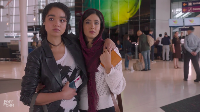 Kat (Aisha Dee) standing with Adena (Nikohl Boosheri) at the airport before she boards a flight to the Middle East.