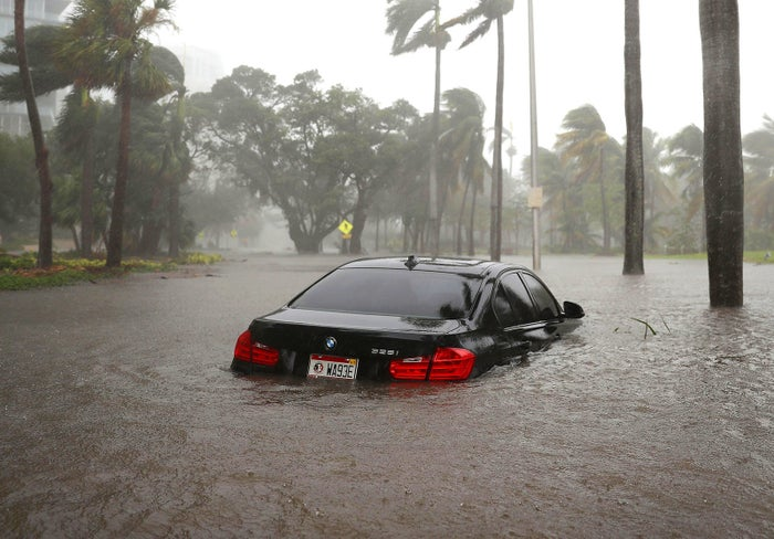 A car is submerged in a flooded street in Miami.