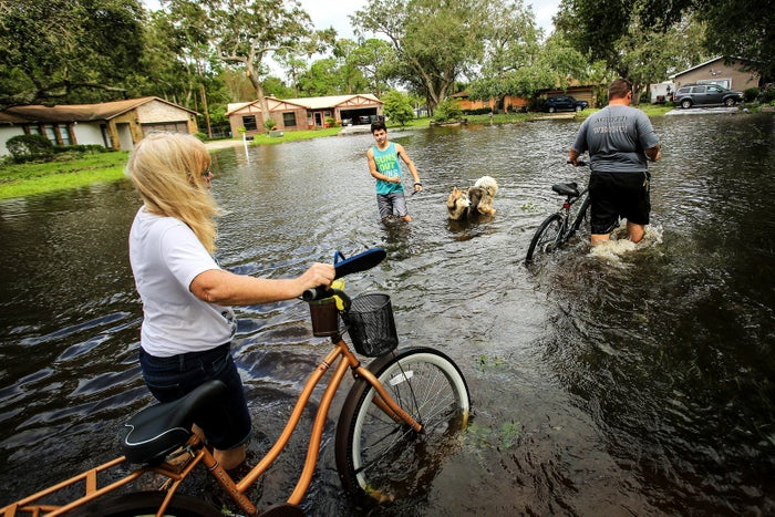 Andrew Myers (R) and his mother-in-law Debbie McCulley (L) pass Brian Rondon and his dog, Zeus, as they walk their bikes through the flooded Brookside Avenue in Kissimmee on Sept. 11.
