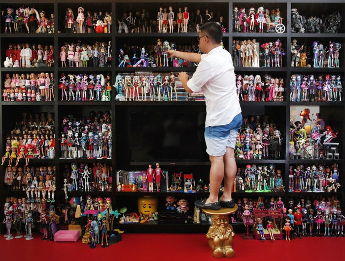 The white exterior and spartan grey staircase of Jian Yang's tidy house gives no hint of the shock that lies within: a pink living room floor and his collection of more than 6,000 Barbie dolls. The 33-year-old Singaporean favors minimalist decor, but the Barbies — and 3,000 dolls of other kinds — dominate three sides of the main room and spill over to fill nine mirrored cabinets in his dressing room and the shelves of his study.