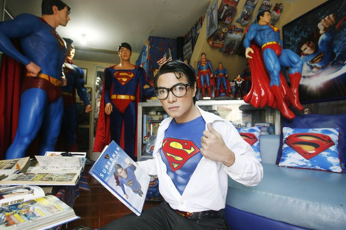 "Herbert Chavez poses with his Superman collection inside his house in Calamba Laguna, Philippines. In his idolization of the superhero, Chavez, a self-professed ""pageant trainer"" who owns two costume stores, has undergone a series of cosmetic surgeries for his face, body, and even his skin color to look more like the ""Man of Steel""."