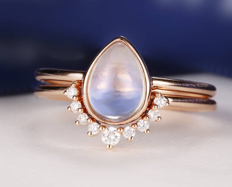 teadrop moonstone on sample band with a matching band that has a cluster of diamonds that go around it