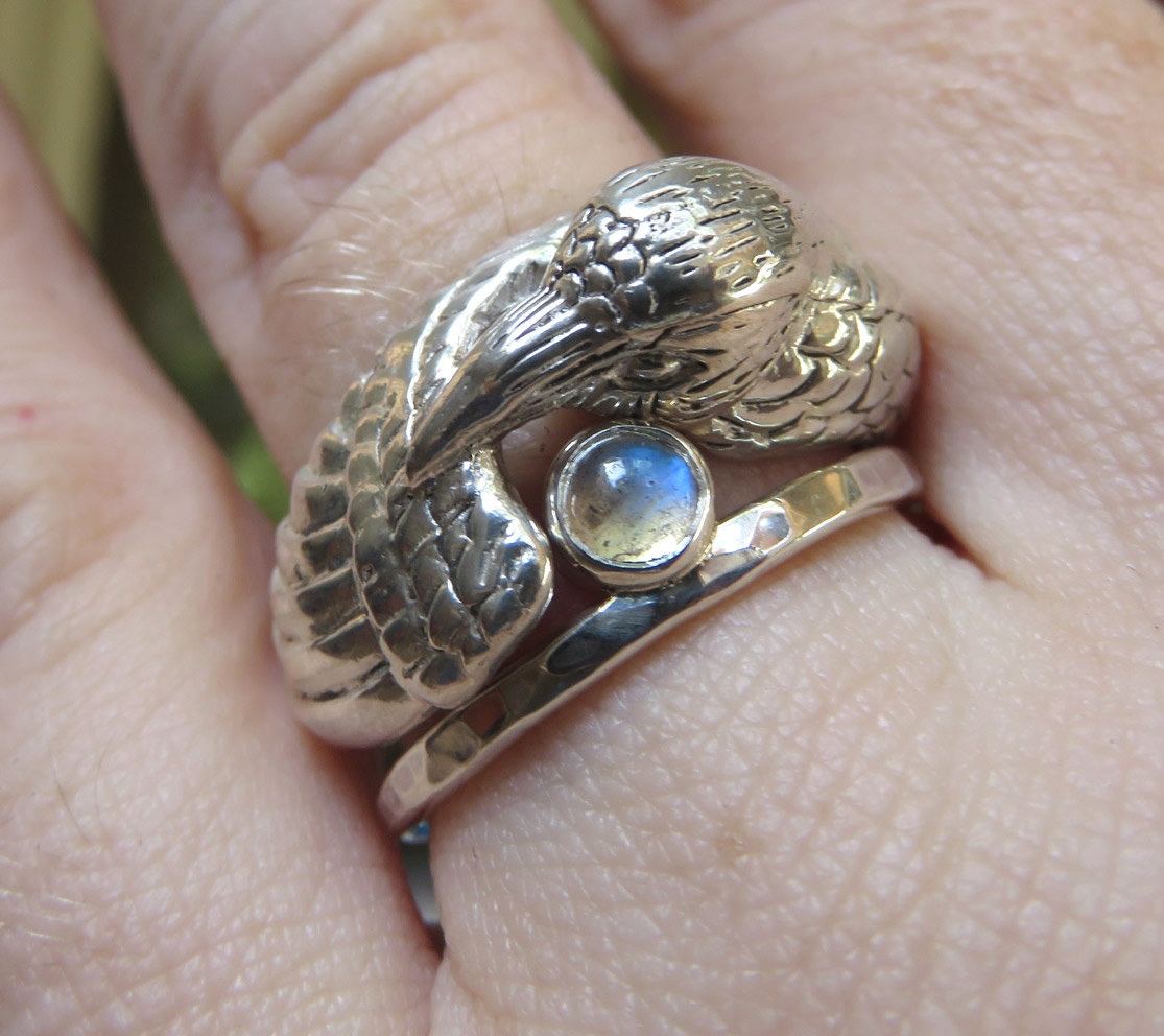 thin silver band with moonstone on top with a stacking raven ring that cuddles with the stone