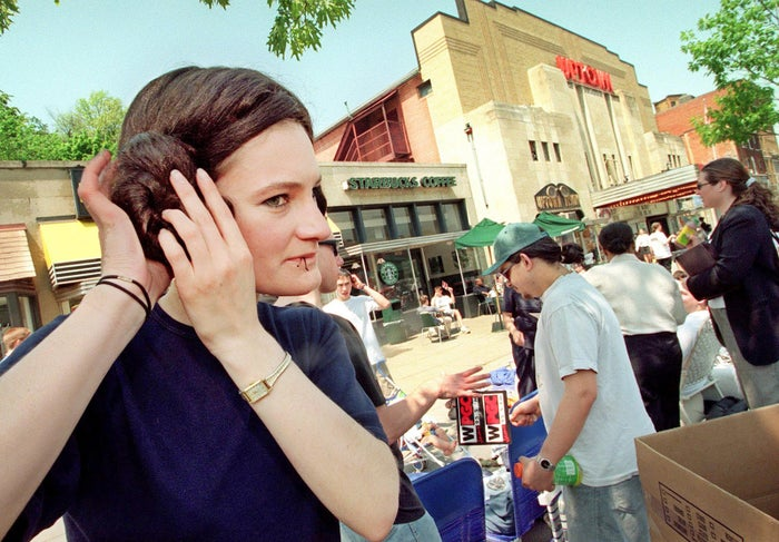 Liz Wohlker from Arlington, Virginia, does her hair like Princess Leia while waiting in line to purchase tickets for Star Wars: Episode I — The Phantom Menace at the Uptown Theater in Washington, DC, on May 12, 1999.