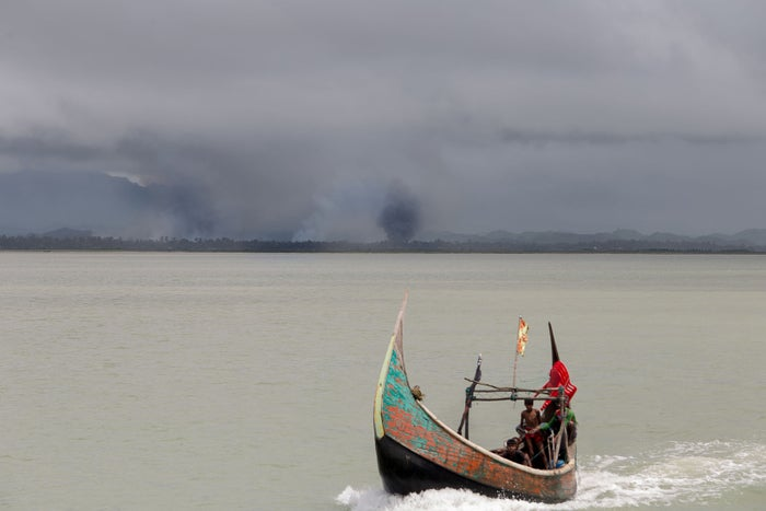 Rohingya refugees arrive at Bangladesh on a boat as smoke rises on the Burmese shorelines behind them.